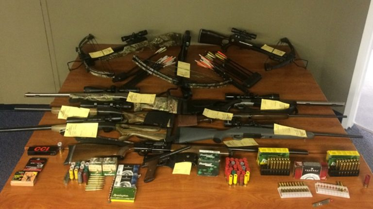 Police display weapons they seized including three crossbows, three shotguns, two muzzleloaders, two rifles, one handgun and a number of arrows and ammunition. (photo courtesy DNREC)