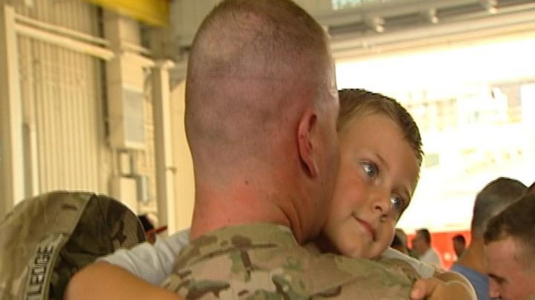 Ryan Ratledge hugs his son after serving with the National Guard in Afghanistan for nearly a year.(Gene Ashley/WHYY)
