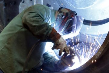 A man welds parts in fans for industrial ventilation systems at the Robinson Fans Inc. plant in Harmony