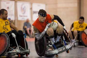 Mason Symons nearly tips his chair in a run to the goal during the championship rugby game at the National Veterans Wheelchair Games. (Brad Larrison/for NewsWorks)