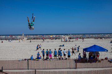 A man goes down a zipline while games of ultimate frisbee are played on the beach in WIldwood, Nj. (Brad Larrison/for NewsWorks)