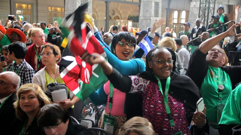 Myriam Mwangi (center) and Katherine Gachanja of Nairobi, Kenya, celebrate as the World Meeting of Families officially opens in the Grand Ballroom of the Pennsylvania Convention Center. (Emma Lee/WHYY)