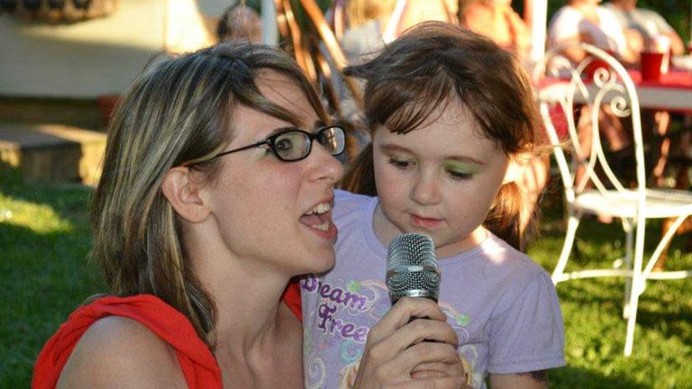 Amy Day speaks at an event with her daughter by her side. (Courtesy of Cheri Collins)