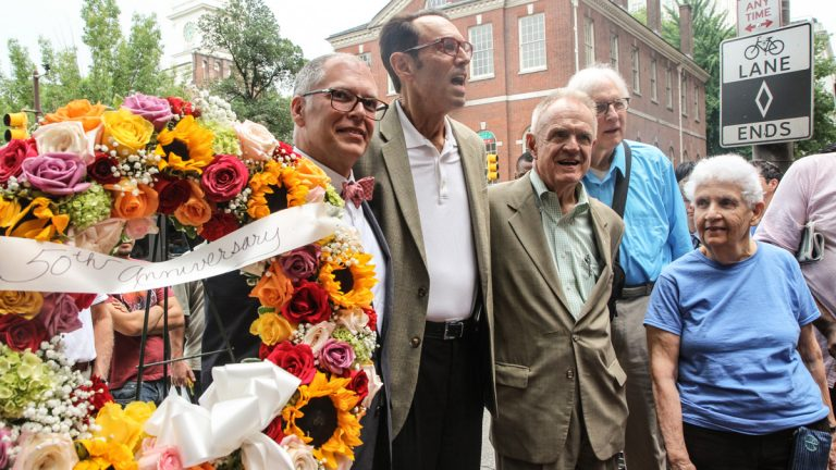 Jim Obergefell, Malcolm Lazin, Paul Kuntzler and Ada Bello place a wreath in front of a Philadelphia plaque honoring LBGT pioneers. (Kimberly Paynter/WHYY)