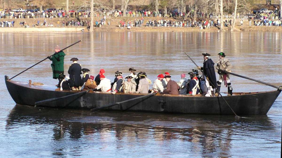 Reenactors make their way across the Delaware in very deep boats, making it appear that the rowers are sitting. (Photo courtesy of Kathleen Pasko)