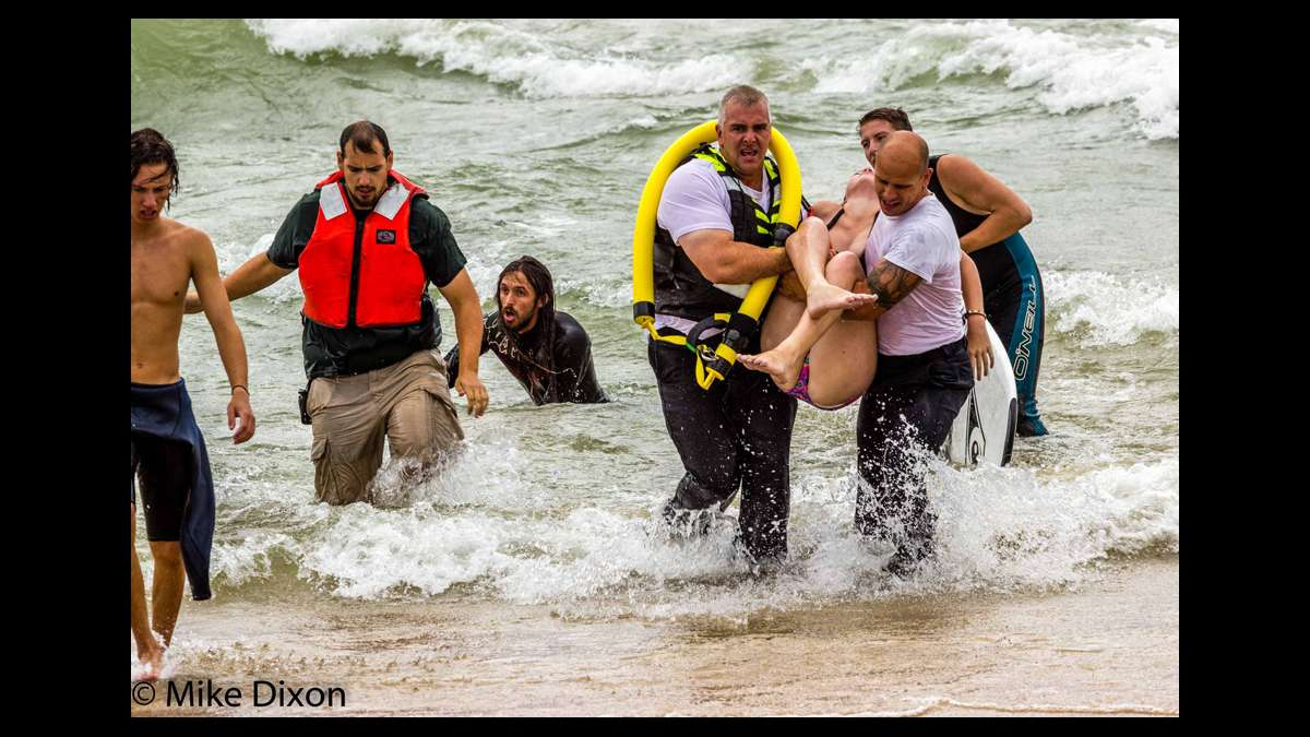 Surfer Zebulon Boeskool (3rd from left) appears exhausted after he and another man saved two distressed swimmers in Lake Michigan on Aug 20