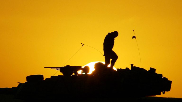 A U.S. soldier walks atop his armored vehicle at sunset as he  prepares for a night military exercise, in the Kuwaiti desert south of the Iraqi border, Sunday, Dec. 22, 2002. (AP Photo/Anja Niedringhaus, file)