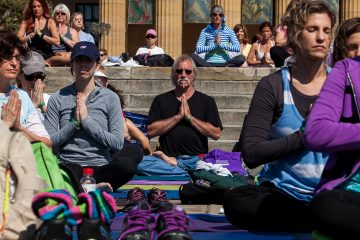 An outdoor yoga class on the steps of the Philadelphia Museum of Art gets underway with a few minutes of reflection. (Brad Larrison/for NewsWorks)