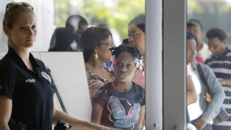 A police officer holds the door as people line up outside the Joe Celestin Center in North Miami, Fla., during the ACA's National Youth Enrollment Day in February. (AP Photo/Wilfredo Lee)