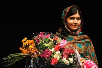 Malala Yousafzai poses with a bouquet after speaking during a media conference at the Library of Birmingham