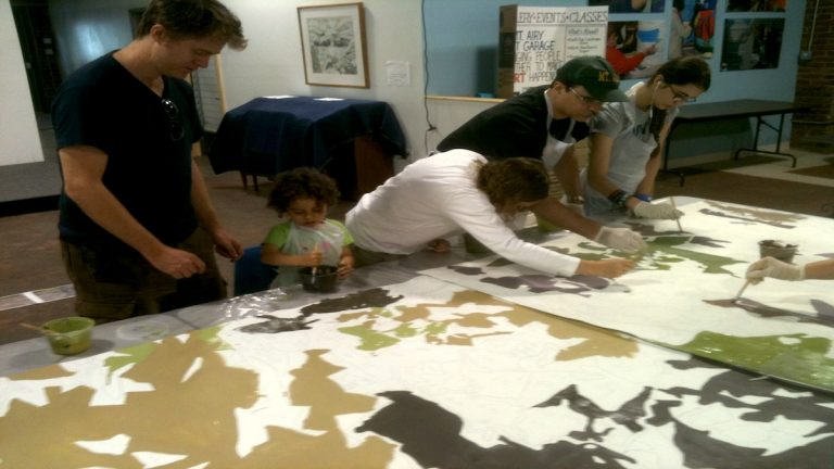 The Kleiner family works on a portion of the mural. (Karl Biemuller/for NewsWorks)