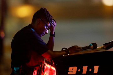 Black police officers, including this Dallas Police officer lamenting the deaths of her colleagues, live conflicted lives. (LM Otero/AP)