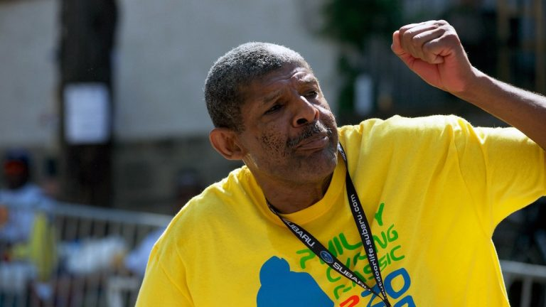Volunteer Melvin Moore, shown here in 2013, cheers on bikers up and down the stretch where the gradient peaks. (Bas Slabbers/for NewsWorks, file)