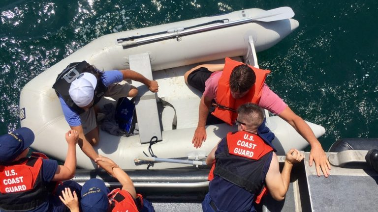 U.S. Coast Guard members help rescue two passengers from a capsized boat off the New Jersey coast Friday morning. (Image courtesy of Sabrina Clarke/U.S. Coast Guard)