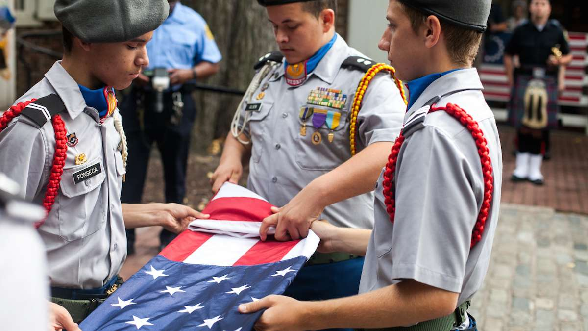 Members of the Frankford High School ROTC Program fold a flag to honor fallen police and firefighters on September 11, 2016.