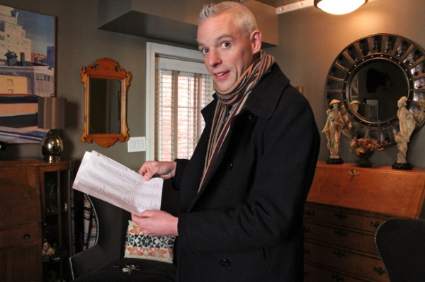 <p>Will Massey, standing in the living room of his Carpenter Street home, holds a list he compiled of 400 properties that have sold in the last year. The city's assessment of their value, he says, are way off. (Emma Lee/for NewsWorks)</p>