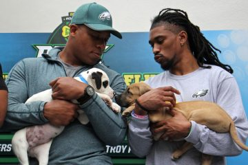 Eagles players Terrill Watson (left) and Ron Brooks hold puppies during the Puppy Bowl draft at Morris Animal Refuge in South Philadelphia. (Emma Lee/WHYY)