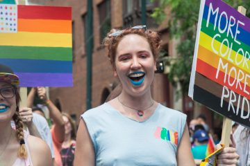 A marcher uses the newly adopted, Philly-introduced pride flag the 2017 Philadelphia Pride Parade, Sunday, June 18, 2017. (Emily Cohen for NewsWorks)