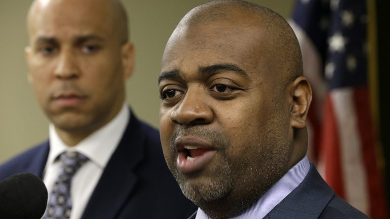 Newark Mayor Cory Booker, left, looks on as Newark Southward Councilman Ras Baraka talks during a news conference, Wednesday, March 27, 2013, in Newark, N.J. (AP Photo/Julio Cortez)