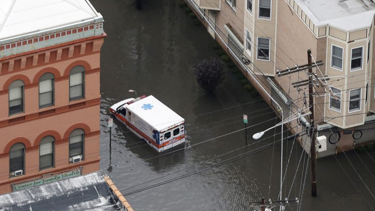 An ambulance drives through a flooded street in Hoboken, N.J. in the wake of Superstorm Sandy on Tuesday, Oct. 30, 2012. (Mike Groll/AP Photo)