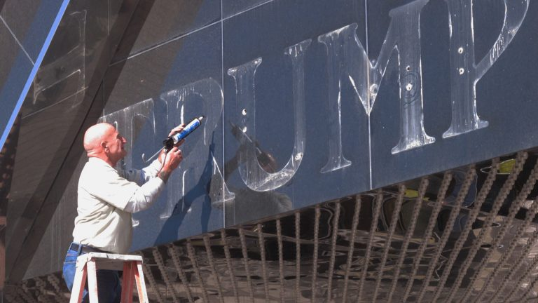 In this Oct. 6, 2014 photo, a worker applies caulk to holes in the facade of the former Trump Plaza casino in Atlantic City N.J (AP Photo/Wayne Parry)