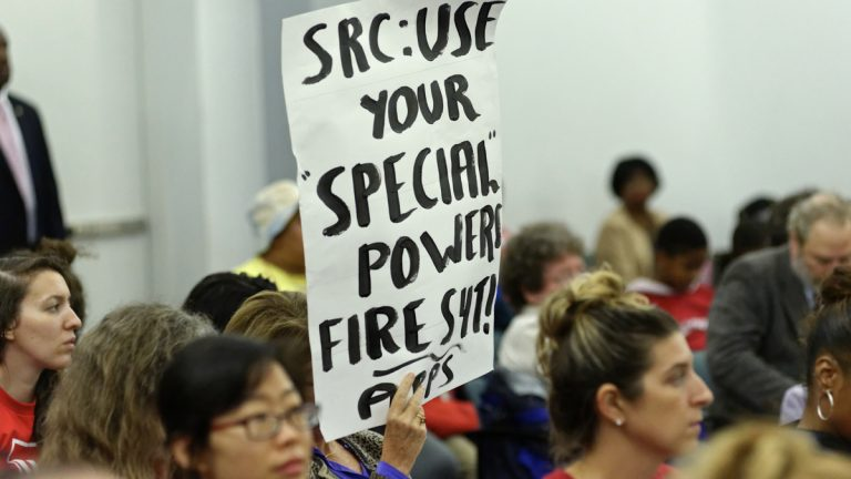 An attendee at November's SRC meeting holds a sign urging the board to get rid of Source4Teachers. (Bastiaan Slabbers/for NewsWorks)