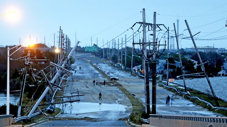 Downed power lines and a battered road is what superstorm Sandy left behind as people walk off the flooded Seaside Heights island, Tuesday, Oct. 30, 2012. (AP Photo/Julio Cortez)