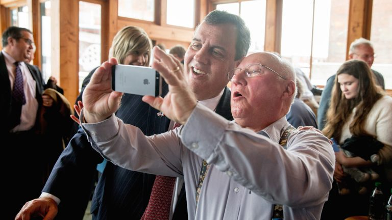 Chris Christie takes a photo with a visitor after speaking at Elly's Tea and Coffee House in Muscatine, Iowa, Tuesday, Dec. 29, 2015. (AP Photo/Andrew Harnik)