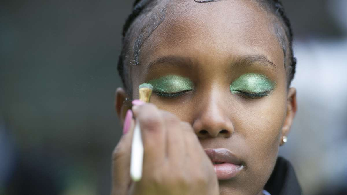 A member of the Second 2 None Drill Team is made up prior to the parade. (Jonathan Wilson/for NewsWorks)