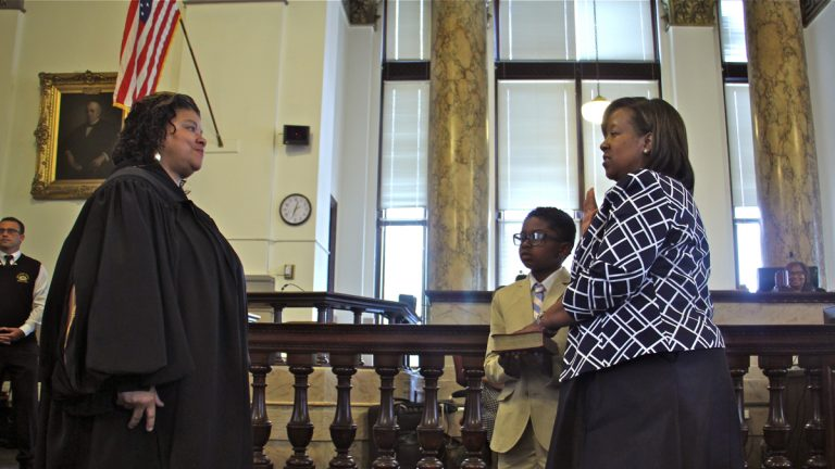 With her son by her side, Kelley B. Hodge is sworn in as Philadelphia District Attorney by Court of Common Pleas Judge Sheila Woods-Skipper. (Emma Lee/WHYY)