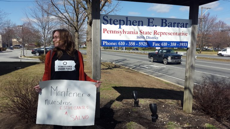 Widener University freshman Hannah Guth protests Pa. House Bill 14 outside of state representative Stephen Barrar's office in Chadd's Ford. (Laura Benshoff/WHYY)