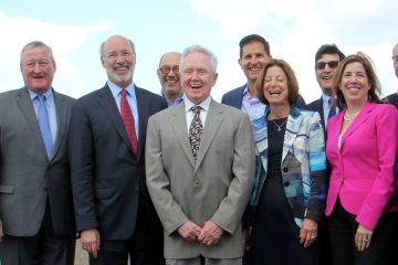 Tom Corcoran (center), outgoing president of the Delaware River Waterfront Corporation, poses for a photo after announcing funding for the Penn's Landing cap and civic space. (Emma Lee/WHYY, file)