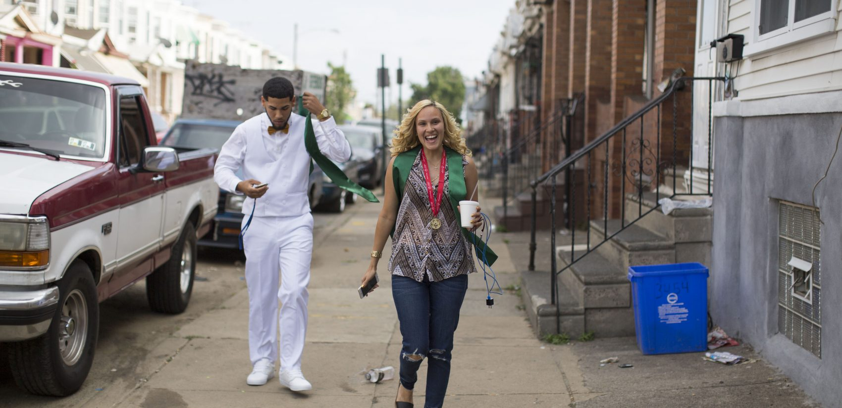 </b> Walking down her block, Savannah beams with pride on graduation day. (Jessica Kourkounis/For Keystone Crossroads)