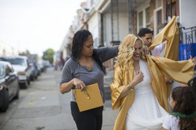 Slideshow: Neverlyn helps her daughter with her graduation gown on the sidewalk in front of their home. (Jessica Kourkounis/For Keystone Crossroads)