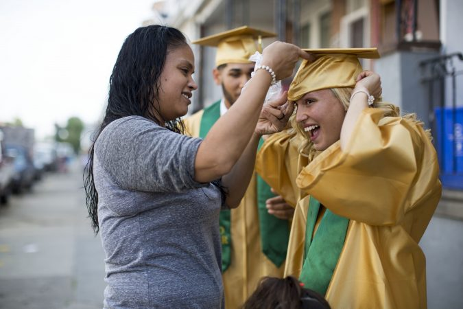 Neverlyn, who dropped out of Thomas A. Edison High School 20 years ago, helps Savannah fit her graduation cap. (Jessica Kourkounis/For Keystone Crossroads)