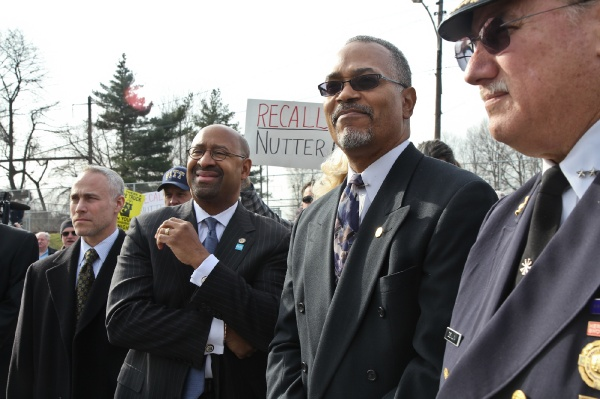 <p>Philadelphia Mayor Michael Nutter looks onto the dedication ceremony of Engine 38 in Tacony while Local 22 protesters shout for his recall. (Kimberly Paynter/WHYY)</p>