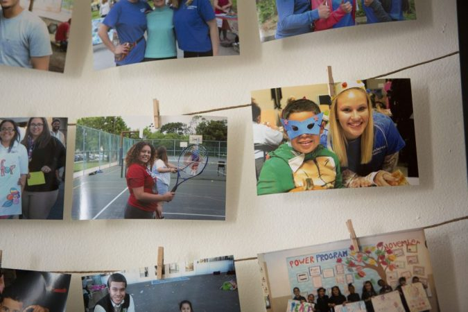 Photos of Providence's teen leaders hang on a wall in their North Philly office. Here, Savannah is pictured (right) during her sophomore year. (Jessica Kourkounis/For Keystone Crossroads)