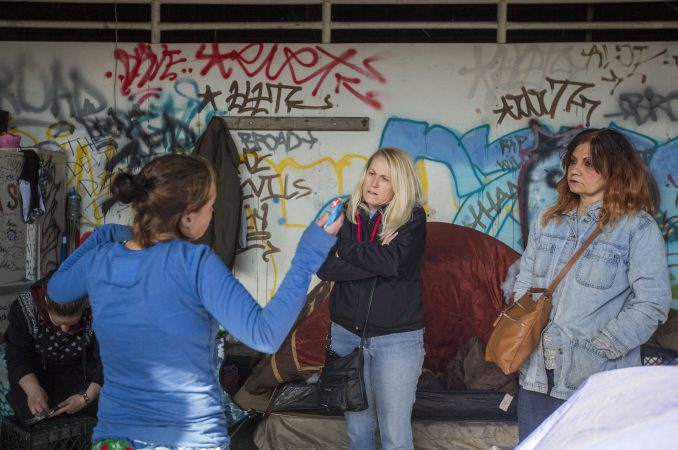 Carol Rostucher (center) and Barb Burns talk to a homeless woman living in an abandoned building in Kensington in Philadelphia. Jessica Kourkounis/For Keystone Crossroads)