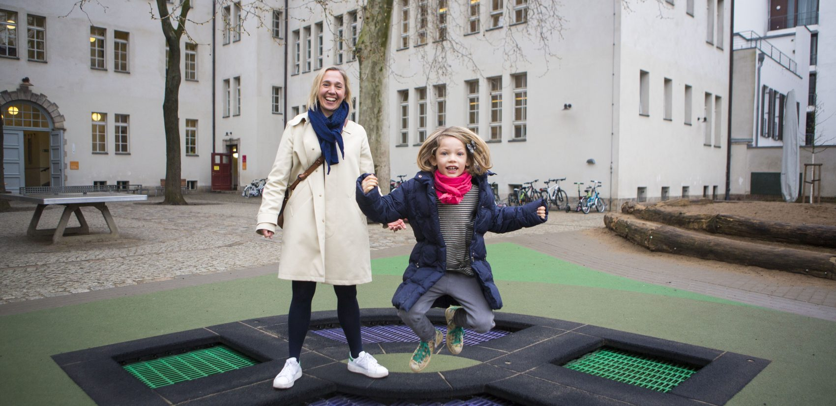 Anke Krause (left) with her daughter Mia in the playground at Koppenplatz elementary where both her daughters attend. (Jessica Kourkounis/For Keystone Crossroads)