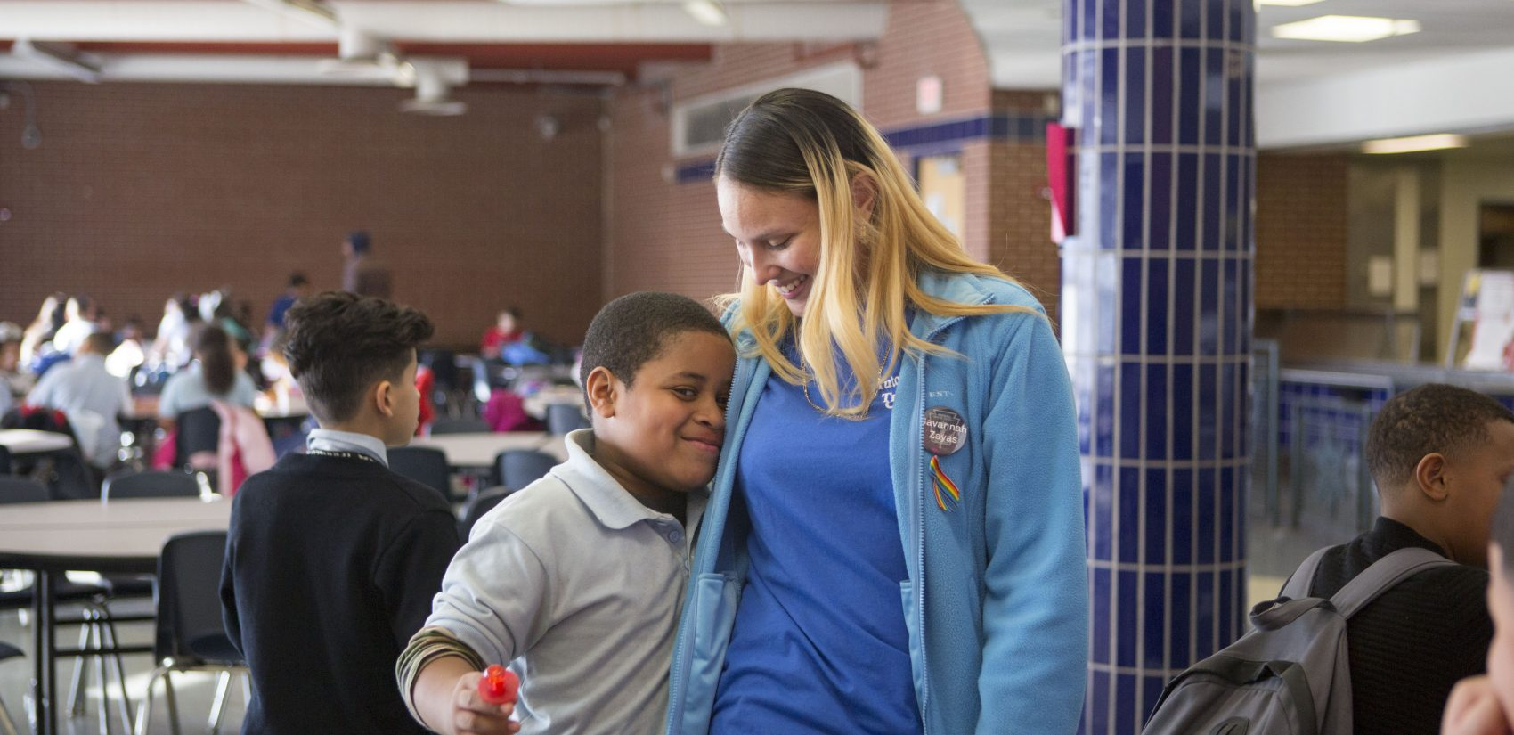 </b> Savannah, in her role as a teen leader in The Providence Center's after school program, hugs an elementary school student. (Jessica Kourkounis/For Keystone Crossroads)