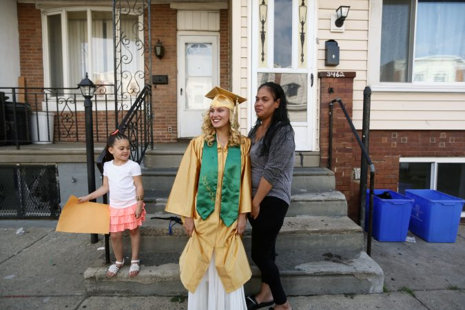 Savannah and Neverlyn pose for pictures outside of their home in Kensington on graduation day as Layla looks on. (Jessica Kourkounis/For Keystone Crossroads)