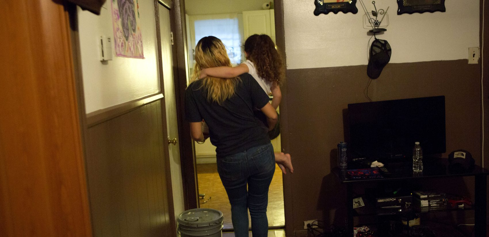 </b> Savannah carries Layla into the kitchen of their Kensington home. (Jessica Kourkounis/For Keystone Crossroads)