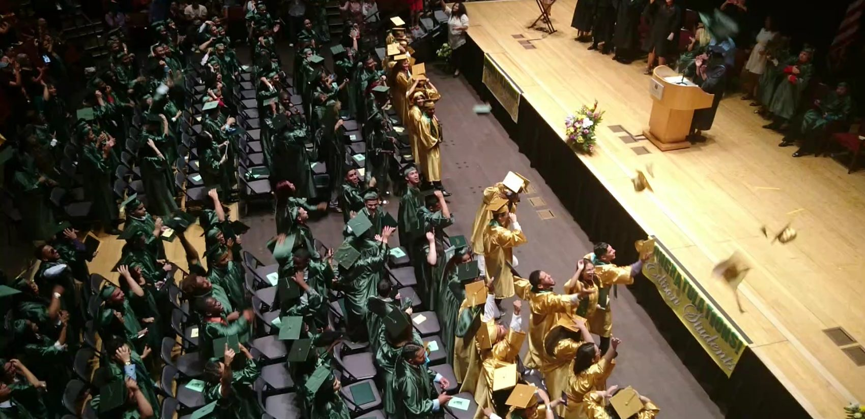 Edison students throw their caps in the air as their rite of passage is made official. Savannah (front row, middle) can be seen hugging a classmate. (Kevin McCorry/WHYY)
