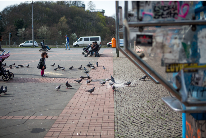 A girl feeds bread crumbs to pigeons in a park in Wedding, Berlin. (Jessica Kourkounis/For Keystone Crossroads)