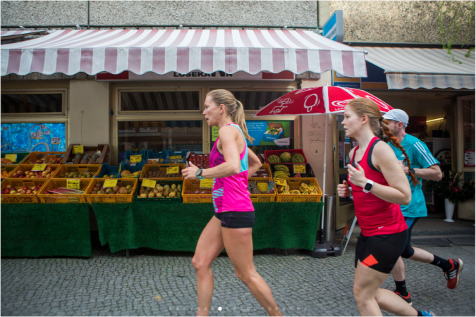 A running club jogs past a quiet fruit stand on the wealthier side of Mitte's social divide. (Jessica Kourkounis/For Keystone Crossroads)