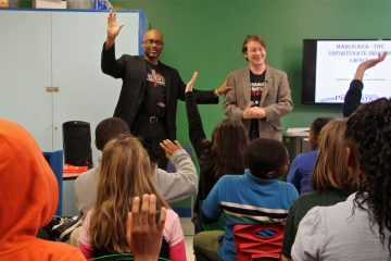 Community prevention coordinators John Hampton (left) and Daniel Elkins present an anti-drug program to children at the Bellevue Community Center in Wilmington, Delaware. (Emma Lee/WHYY)