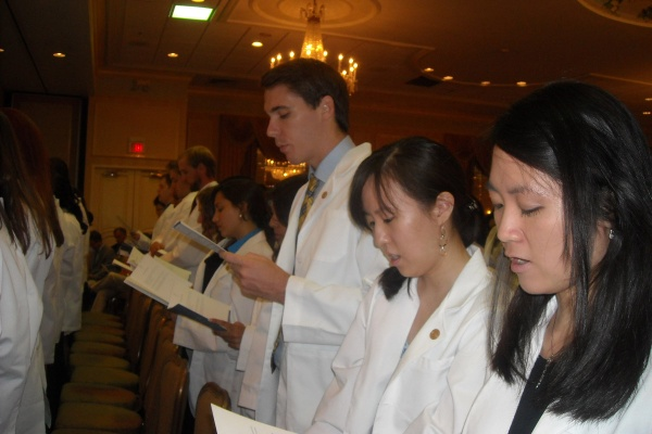 First-year students stand to take the Oath of Hippocrates during the White Coat Ceremony for the Drexel University College of Medicine.