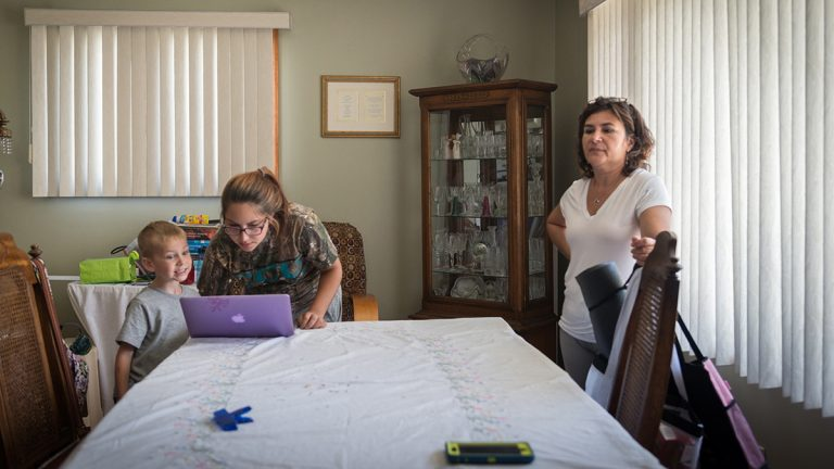 Alessia and her son Jared stand over her computer in grandmother Carmelina Mattioli's house in Glassboro