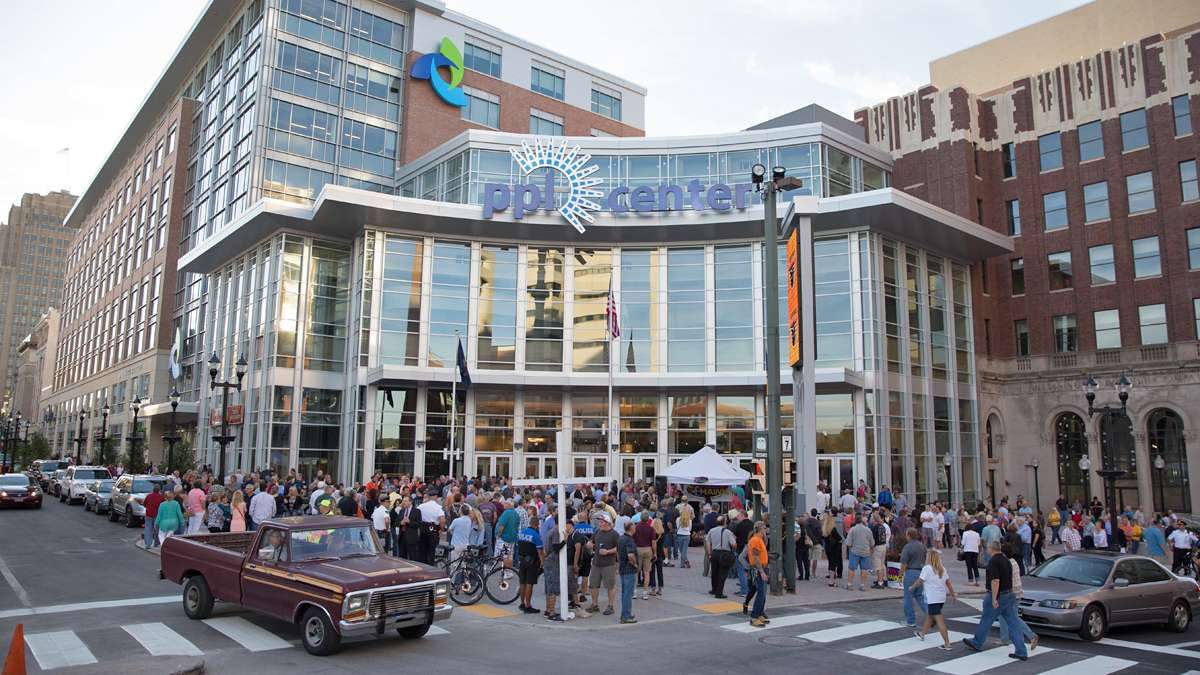 Crowds gather outside of the PPL Center in downtown Allentown for opening night — a sold out Eagles concert.  The arena is home to the Lehigh Valley Phantoms hockey team and is the heart of the city's Neighborhood Improvement Zone.  (Lindsay Lazarski/WHYY)