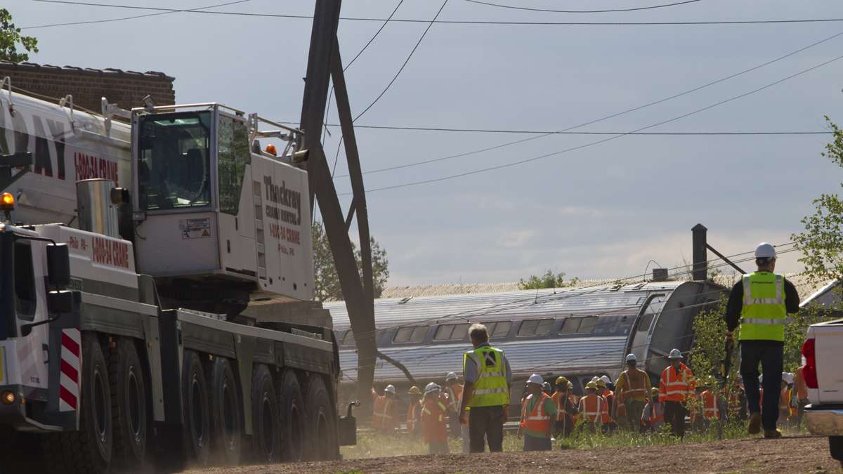 Emergency personnel bring in a crane to move the derailed Amtrak train near Port Richmond in North Philadelphia Wednesday morning. (Brad Larrison/for NewsWorks)